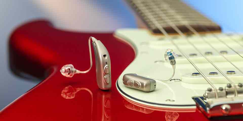 The new Bernafon Viron miniRITE T R lithium-ion rechargeable hearing aids on a red electric guitar showing reflections.