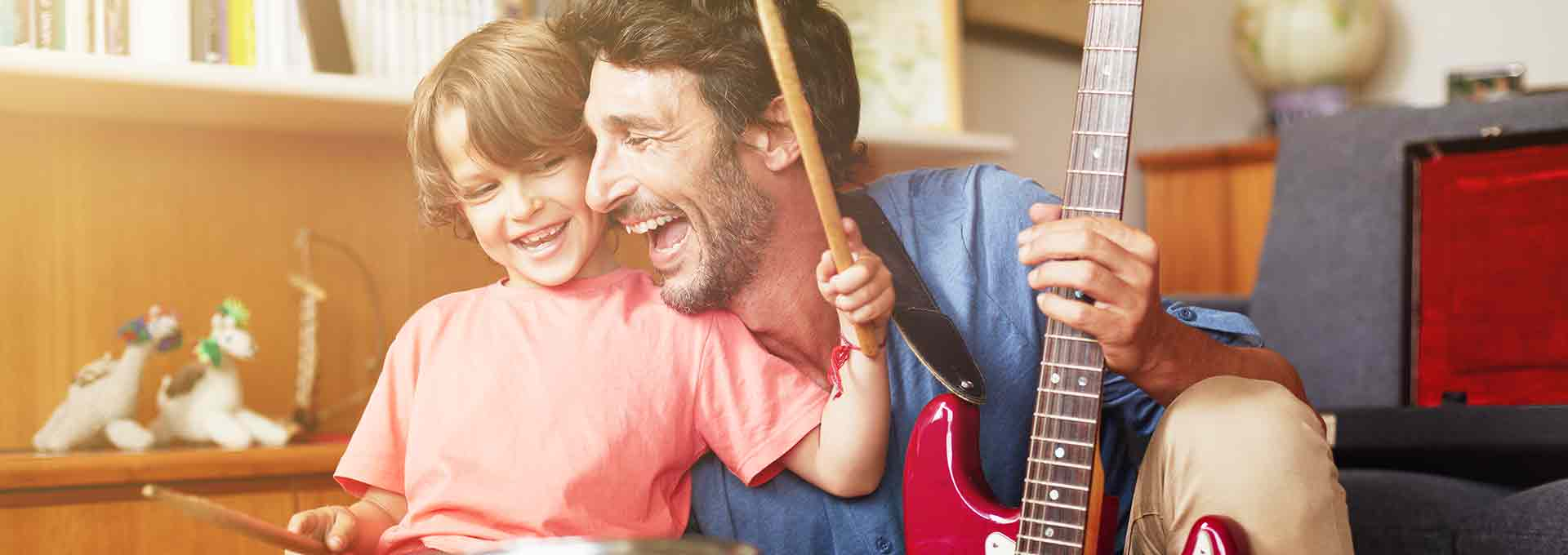 Father with Bernafon Viron hearing aids playing guitar with his five year old son playing the drums and enjoying the moment.