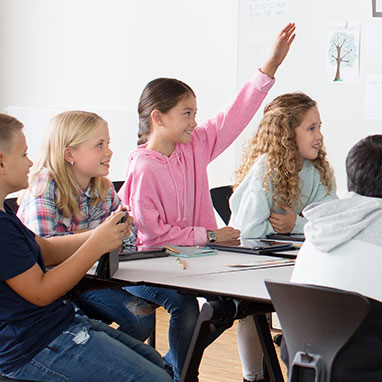 Child wearing Opn play hearing aids raising hand in classroom