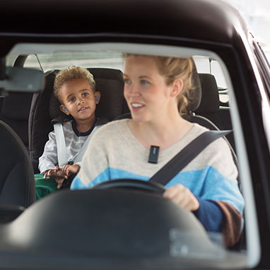Woman wearing Connectclip hearing aid accessory in the car