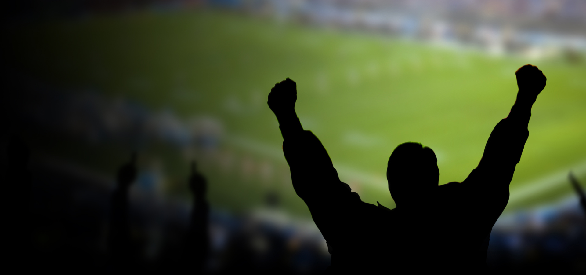 man with arms outstretched in noisy football stadium -1920x900