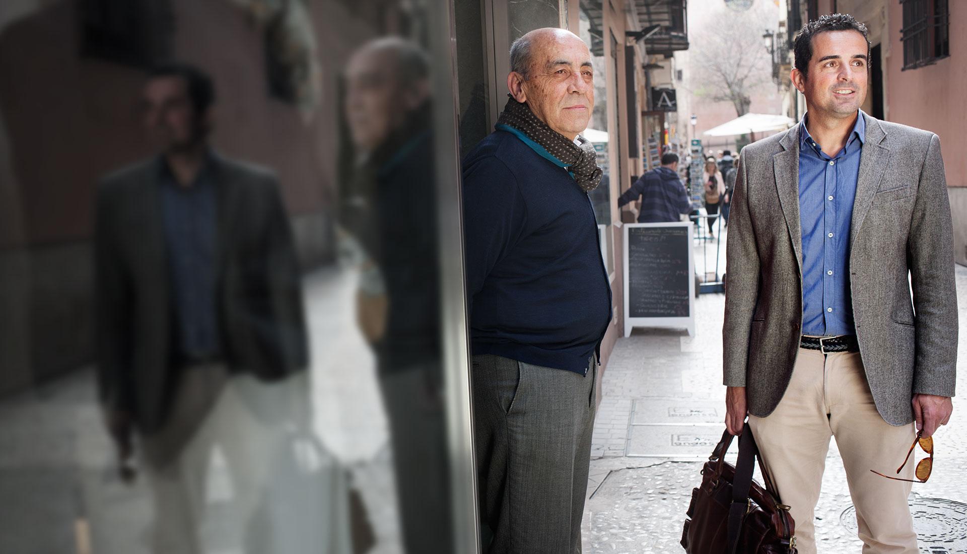 deux hommes discutent dans une rue commerçante