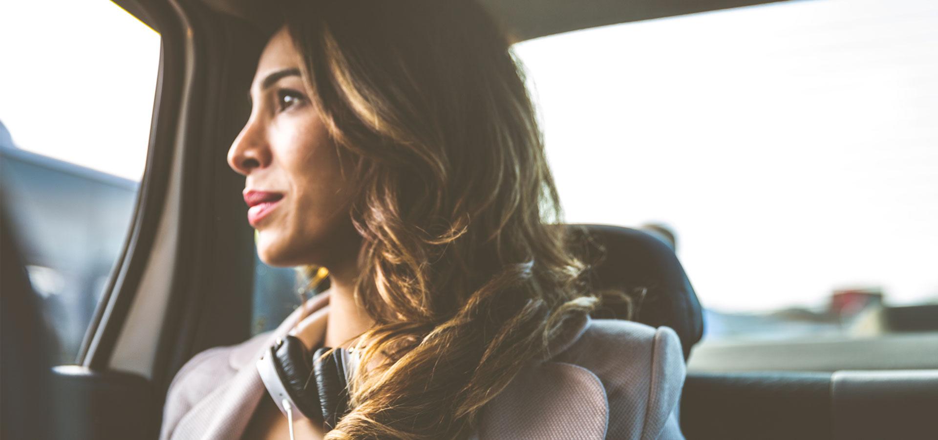 femme aux cheveux ondulés dans une voiture regardant par la fenêtre