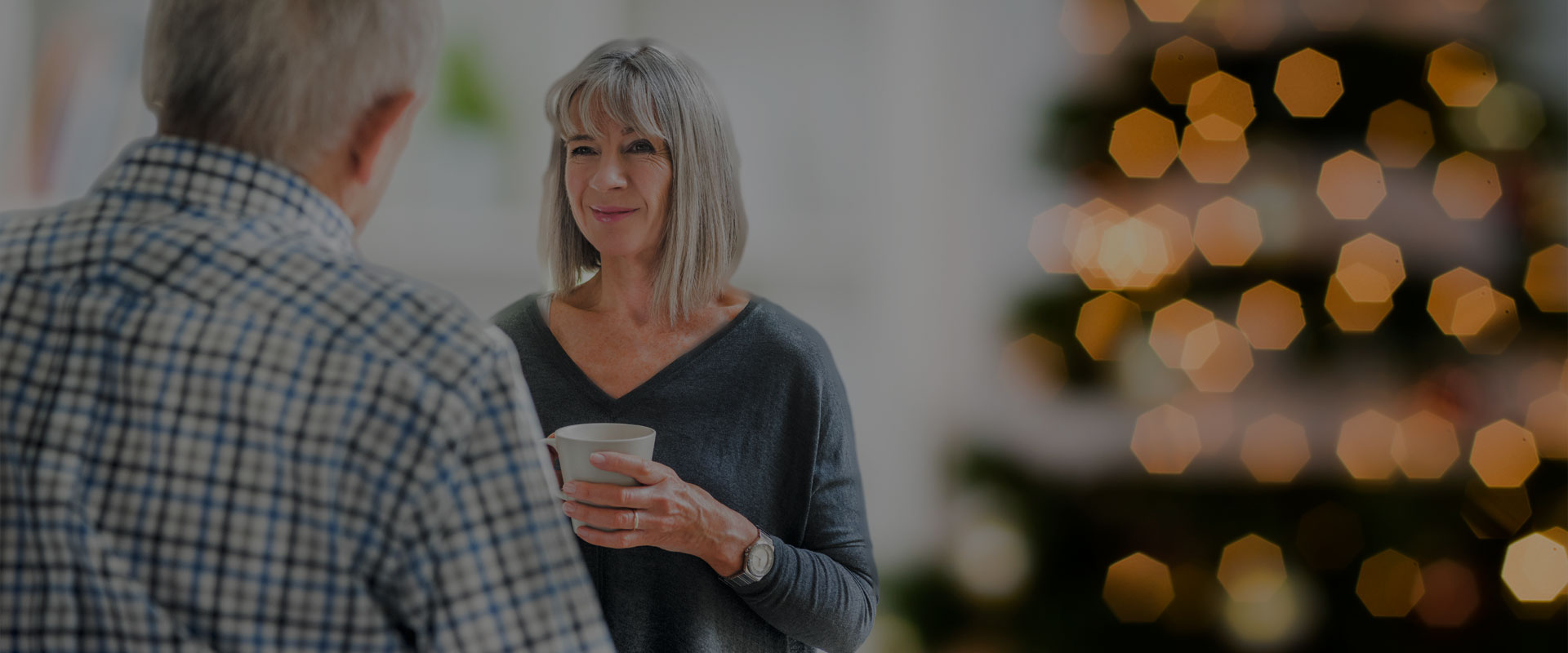 deux personnes un homme et un femme tenant un thé dans ses mains parlent devant un sapin de Noël
