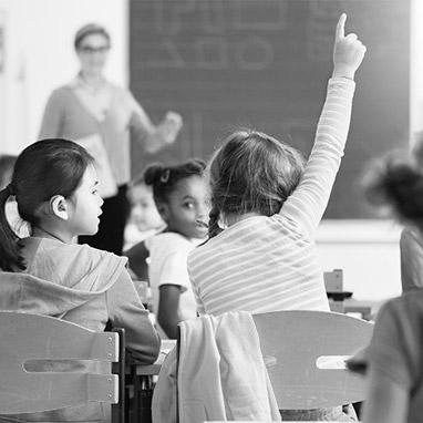 enfants à l'école avec professeur lisant un livre