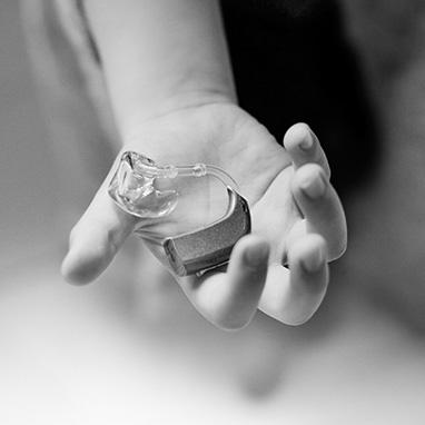main d'enfant portant un appareil auditif