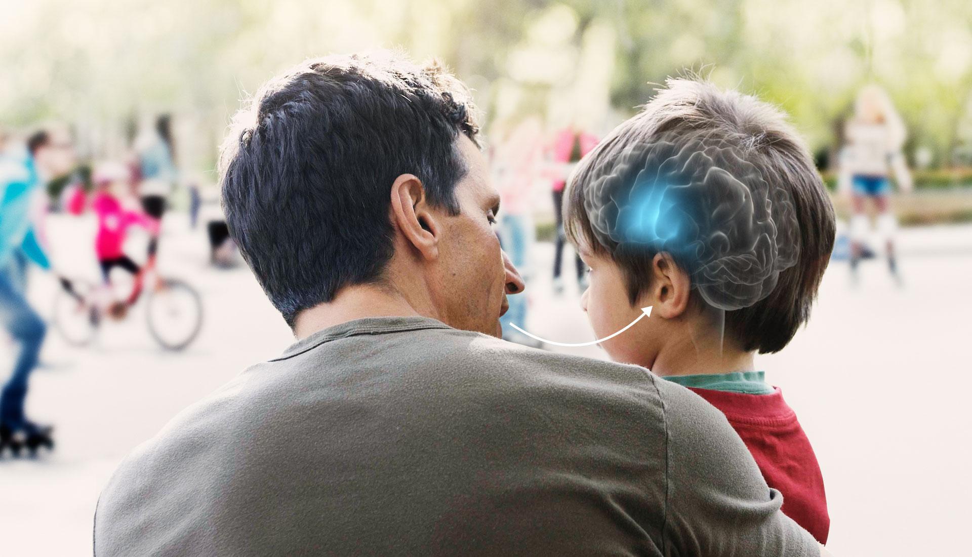 jeune petit garçon dans les bras de son père avec aide auditive et cerveau bleu illuminé