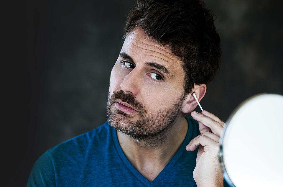 jeune homme hipster barbu se nettoyant les oreilles avec un coton tige